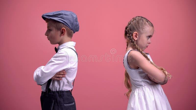 Kränkta ungar kopplar ihop att stå tillbaka i tystnad efter grälar, rosa bakgrund royaltyfria bilder