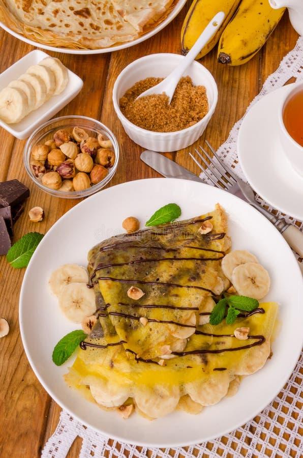 Kräppar eller pannkakor med chokladpralin, bananer och hasselnötter för frukost arkivbilder