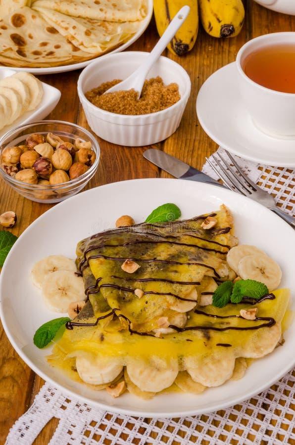 Kräppar eller pannkakor med chokladpralin, bananer och hasselnötter för frukost royaltyfria foton