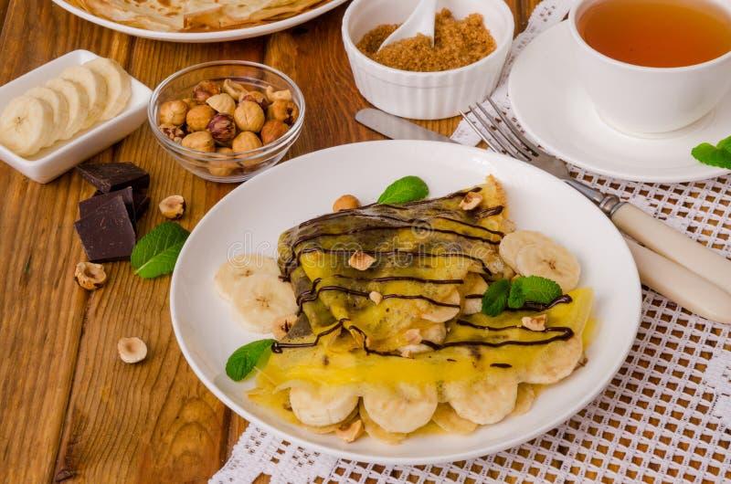 Kräppar eller pannkakor med chokladpralin, bananer och hasselnötter för frukost royaltyfria bilder