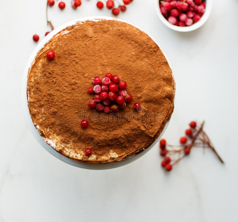 Kräppkaka med smörkräm och kakao och redcurrant på en vit bakgrund, bästa sikt royaltyfria foton