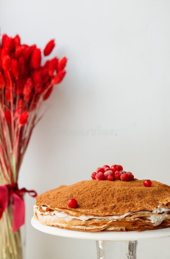 Kräppkaka med smörkräm och kakao och redcurrant på en vit bakgrund med torkade blommor arkivbild