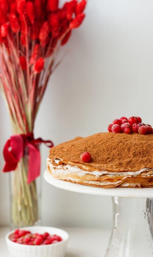 Kräppkaka med smörkräm och kakao och redcurrant på en vit bakgrund med torkade blommor arkivfoto