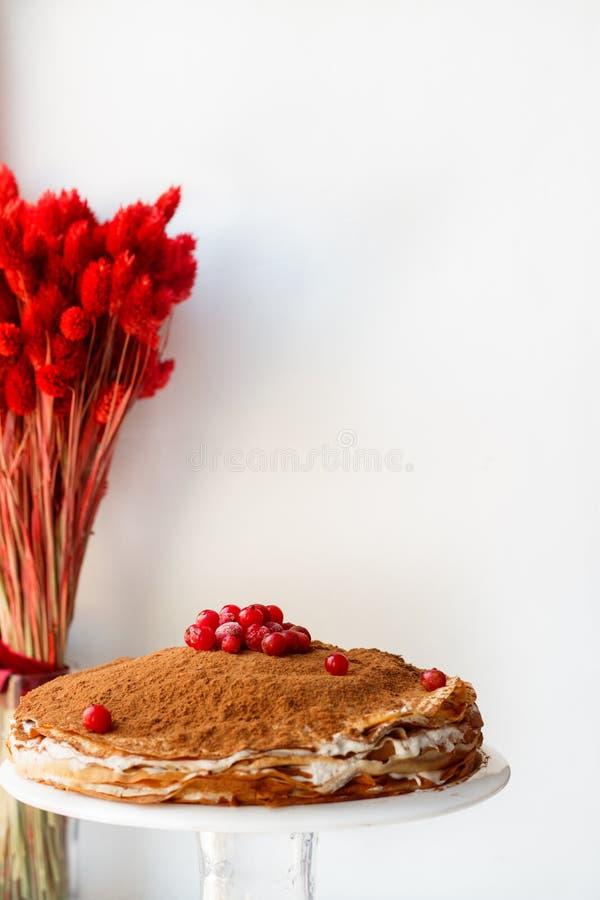 Kräppkaka med smörkräm och kakao och redcurrant på en vit bakgrund med torkade blommor royaltyfri foto