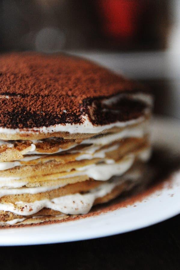 Kräppkaka med tiramisufyllning som dammas av med kakao i pulverform Vit platta, bakgrund av kaffehuset Halvt kakaslut upp fotografering för bildbyråer