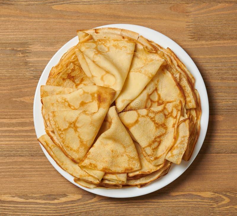 Kräuseln Sie Nahaufnahme, Haufen von dünnen Pfannkuchen auf einem Teller, hölzerner Hintergrund stockbilder