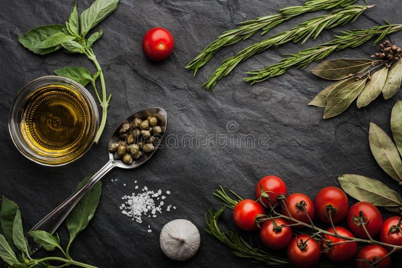 Kräuter mischen mit Tomaten und Olivenöl auf der schwarzen Steintabelle lizenzfreie stockfotos
