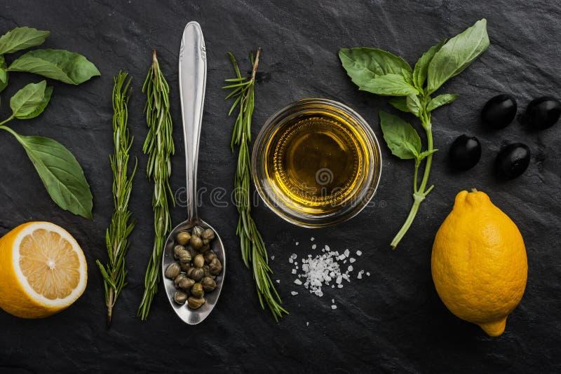 Kräuter mischen mit Zitronen, Kapriolen und Oliven auf der schwarzen Steintabelle stockbilder