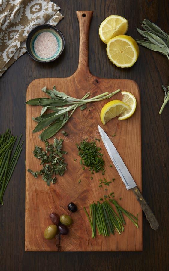 Kräuter, Oliven und Zitronen schneiden und auf einem hölzernen Schneidebrett zugebereitet lizenzfreies stockfoto