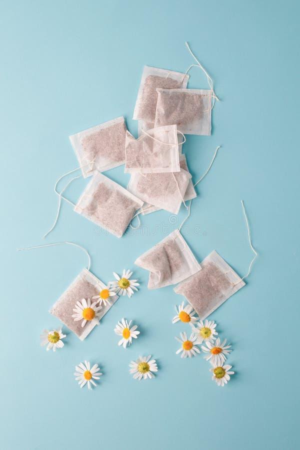 Kräuteralternativmedizin-Reihe: Kamillenblumen und -teebeutel auf blauem Hintergrund Saisonantikrise, Magen und Kälten stockbilder