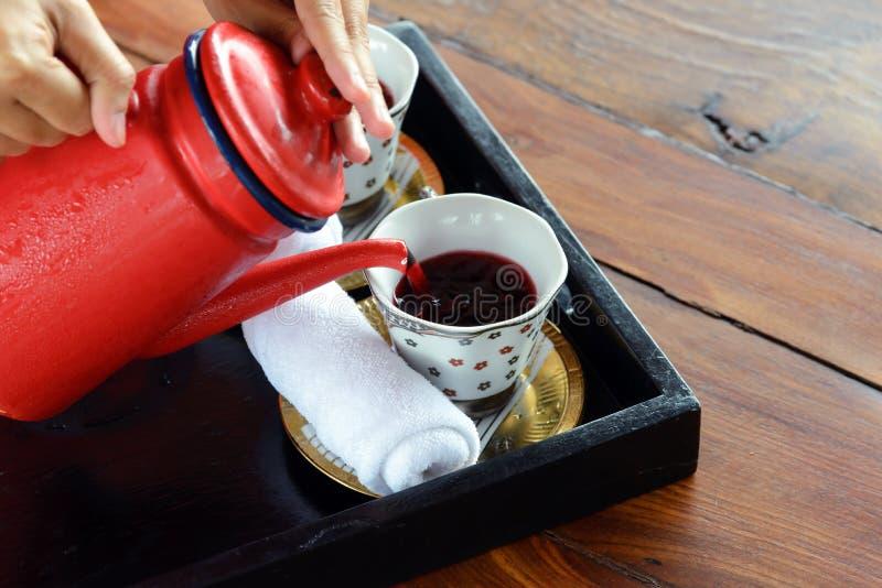 Kräutergetränke gemacht von Roselle-Saft, vom Lemongras und vom süßen Basilikum mit kalten Tüchern - Kellnerin gießt Begrüßungsge lizenzfreies stockbild