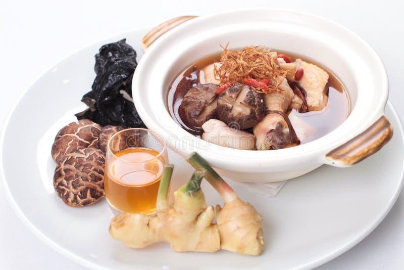 Kräutersuppe des traditionellen Chinesen mit Huhn und rohe Bestandteile auf der Seite stockfoto
