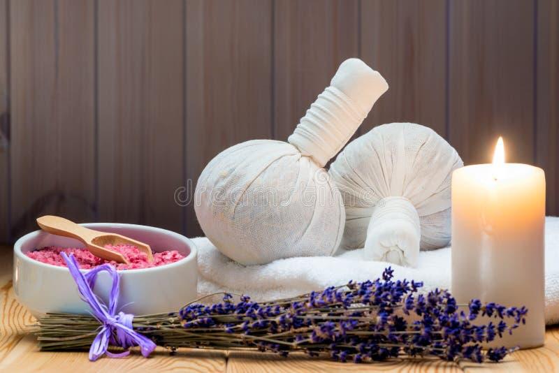 Kräutertaschen mit natürlichem Lavendel und Seesalz mit einer brennenden Kerze für einen Badekurort stockbild