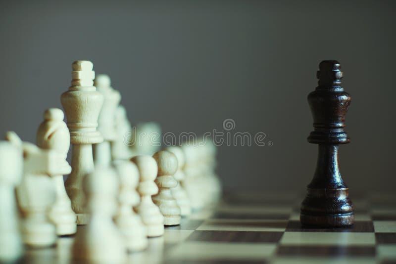 Królewiątek spotkania przeciw potężnemu konkurentowi zespalają się w szachowej grą, biznesowy konkurencyjny pojęcie obraz stock