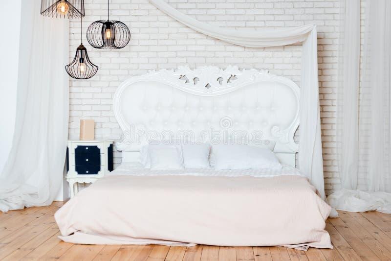 Królewiątka wielkościowy łóżko w loft mieszkaniu Loft stylowa sypialnia z białym projektem zdjęcia stock