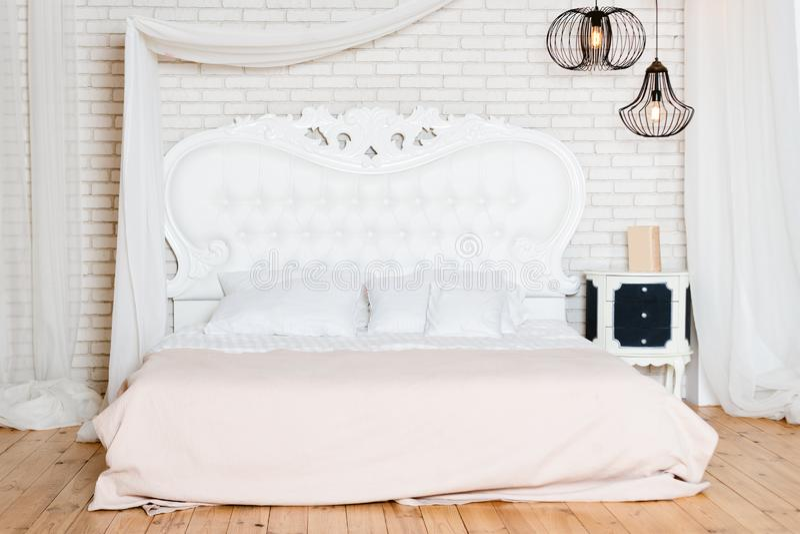 Królewiątka wielkościowy łóżko w loft mieszkaniu Loft stylowa sypialnia z białym projektem zdjęcie stock