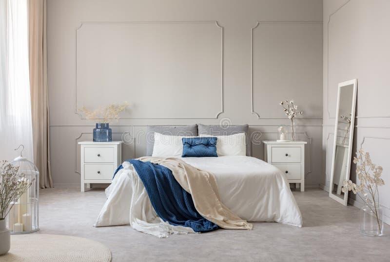 Królewiątka wielkościowy łóżko z popielatą, błękitną i białą pościelą między dwa drewnianymi nightstands z kwiatami w wazach, kop zdjęcia stock