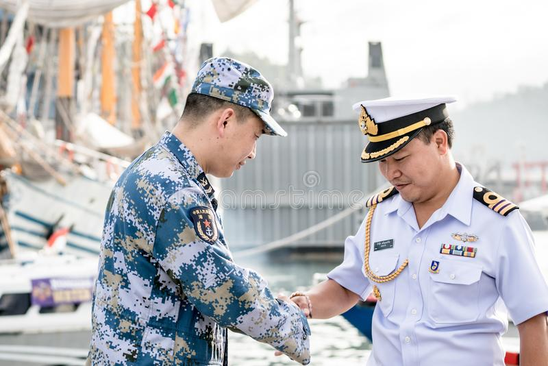 Królewski Tajlandzki marynarka wojenna oficer w bielu munduru potrząśnięć ręce z planu oficerem w błękitnym cyfrowym kamuflażu wz zdjęcia royalty free