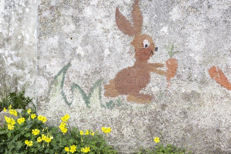 Królik z marchewkami malować dzieciakami na obieranie ścianie starzał się czasem fotografia stock