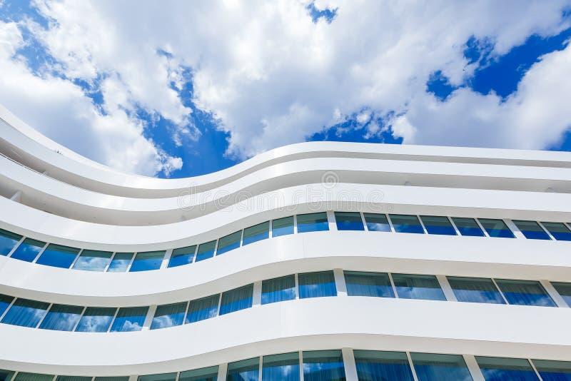 Krökt exponeringsglasyttersida av modern kontorsbyggnad på en bakgrund för blå himmel arkivbild