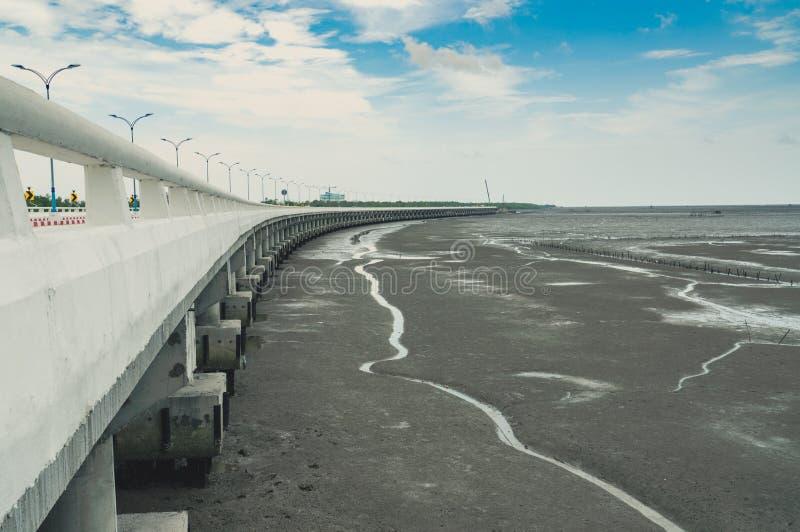 Krökt kust- konkret huvudvägväg med lägre vatten i gyttjastranden med blå himmel och moln Lopp för vägtur Sommarresa royaltyfri bild