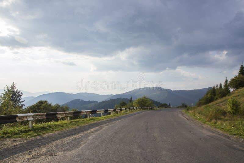 Krökt slingrande bergskogväg i ukrainskt Carpathian Asfaltera huvudvägar och berg under den blåa himlen tomt arkivbild