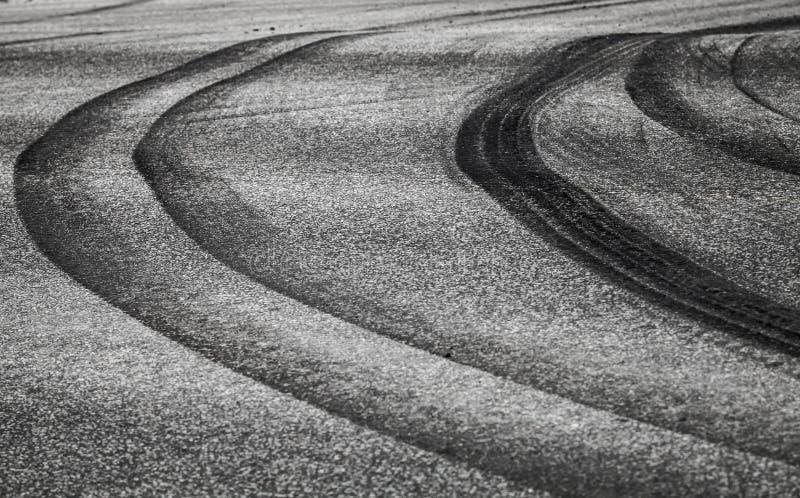 Krökta gummihjulspår på den mörka asfaltvägen royaltyfri fotografi