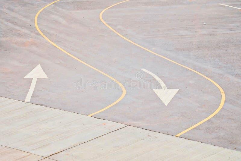Krökta linjer för gul trafik och vitt pilsymbol på vägen arkivfoto