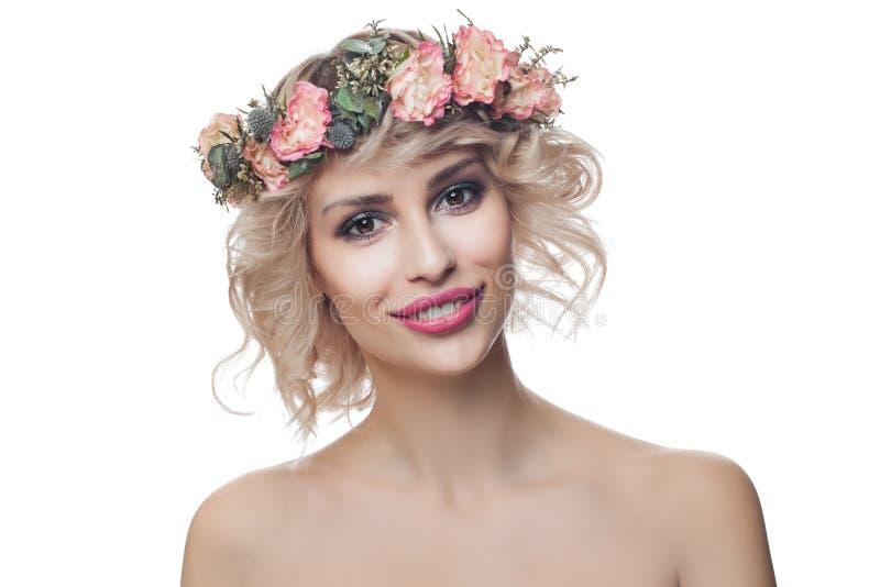 Krönar bärande blommor för härlig lycklig modellkvinna isolerat på vit bakgrund Lockigt hår, makeup och blommor arkivbild