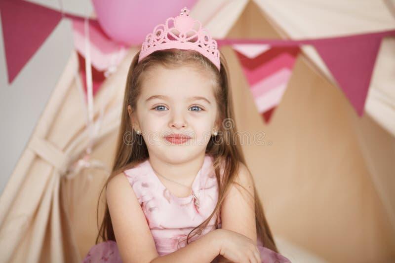 Krönar klär den roliga lilla prinsessaflickan för closeupen i rosa färger och arkivbild