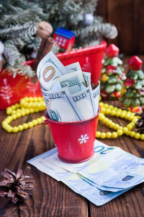 Kręceni rachunki dolary i euro w czerwonych bożych narodzeniach forsują, euro i menchii macaroons, Nowego Roku ` s prezenty zdjęcia royalty free