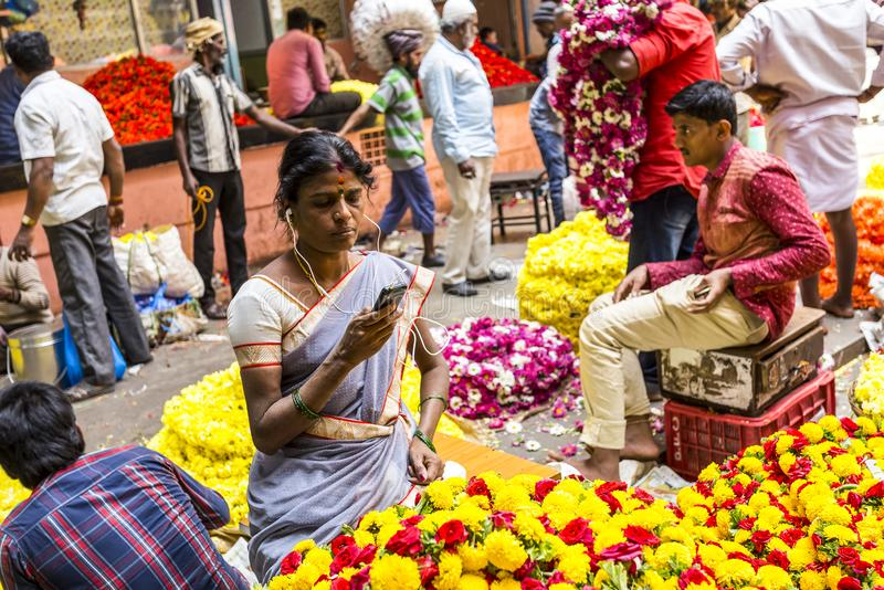 KR Flower Market, Bangalore, India. Women flower vendor, listening to music, in a crowded day at the colorful KR flower market in Bangalore, Karnataka, India royalty free stock photography