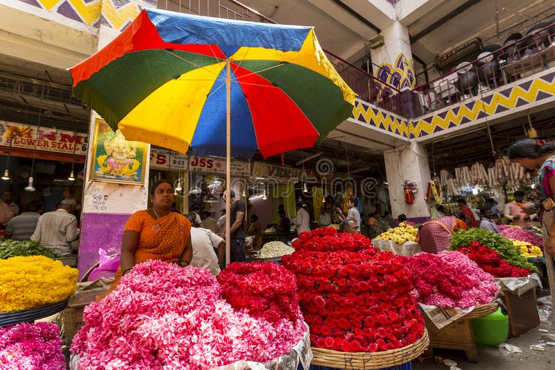 KR Flower Market, Bangalore, India. Women flower vendor, standing under umbrella, in a crowded day in the colorful KR flower market in Bangalore, Karnataka stock photo