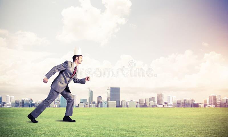 Kr?lewi?tko biznesmen w eleganckim kostiumu bieg na zielonej trawie i nowo?ytny pejza? miejski przy t?em zdjęcia stock