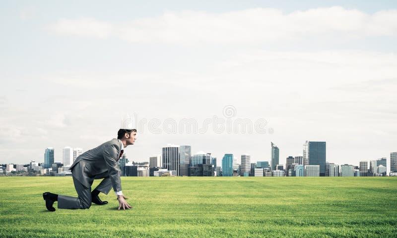 Kr?lewi?tko biznesmen w eleganckim kostiumu bieg na zielonej trawie i nowo?ytny pejza? miejski przy t?em obraz royalty free