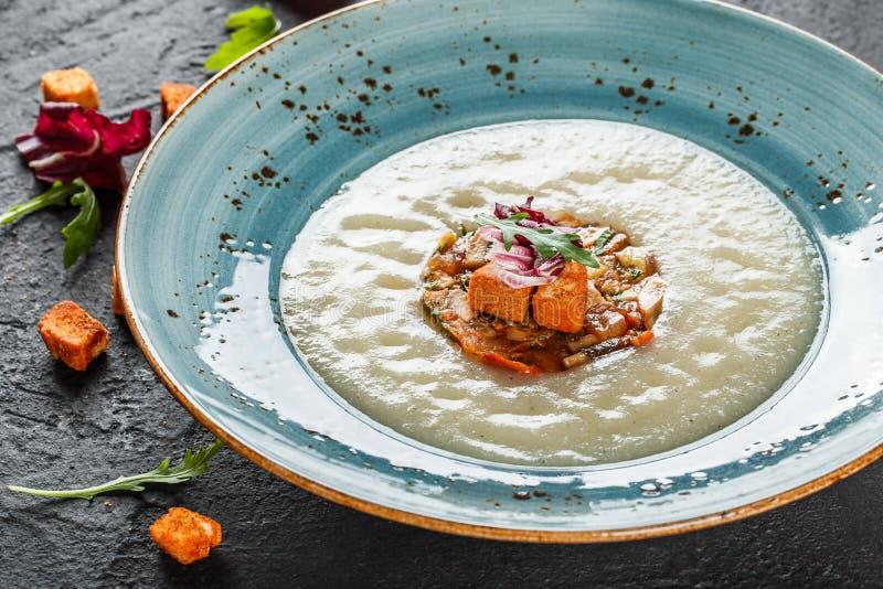 Kr?m- soppa av selleri med tartare fr?n bakade gr?nsaker som dekoreras fr?n krutonger och arugula i platta p? m?rkerstenbakgrund arkivfoton
