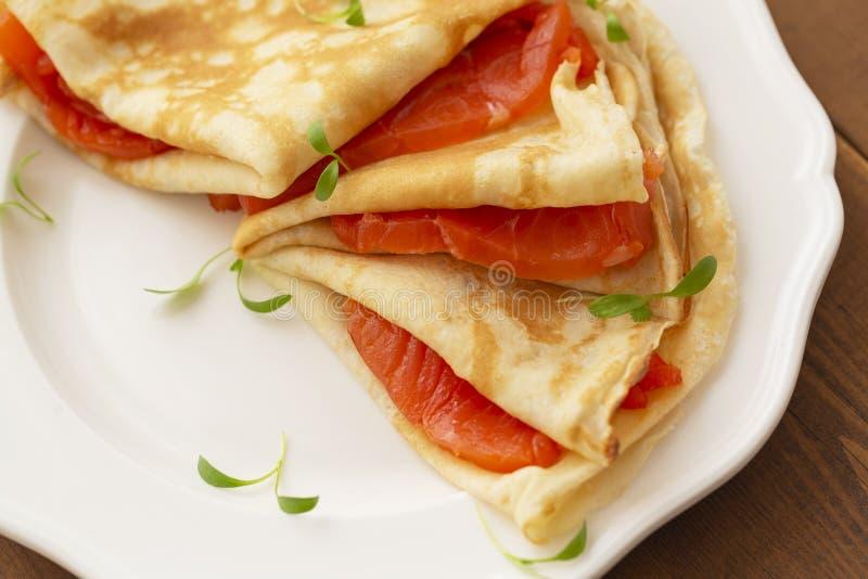 Kr?ppar med den r?kte laxen p? en vit platta L?cker och sund frukost arkivbild