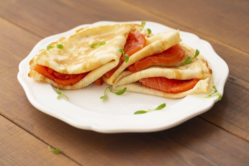 Kr?ppar med den r?kte laxen p? en vit platta L?cker och sund frukost royaltyfria bilder