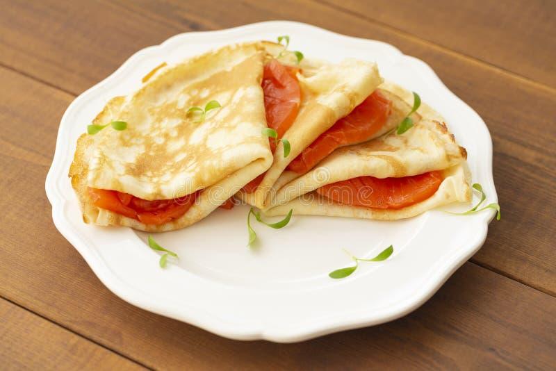 Kr?ppar med den r?kte laxen p? en vit platta L?cker och sund frukost arkivfoton