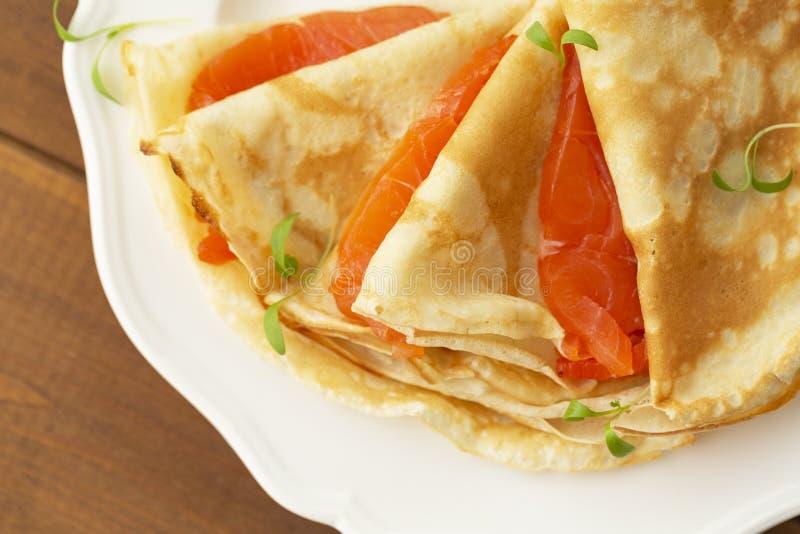 Kr?ppar med den r?kte laxen p? en vit platta L?cker och sund frukost royaltyfri fotografi