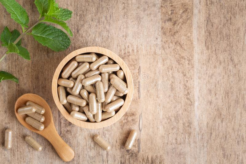 Kr?uterkapseln in der Schale auf Holztischhintergrund Draufsicht von Medizin für gesundes und Kapseln der Löffel hölzern stockbild