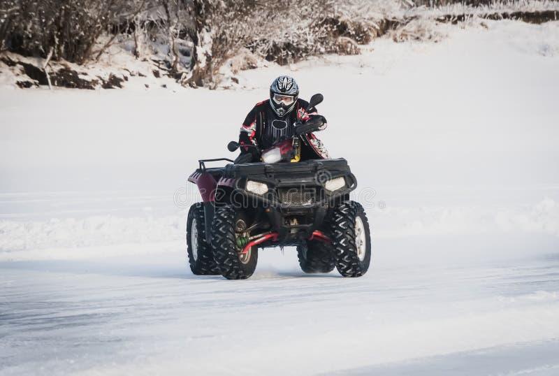 krańcowy Moto jeździec w przekładni na ATV w zimie w śniegu zdjęcia stock