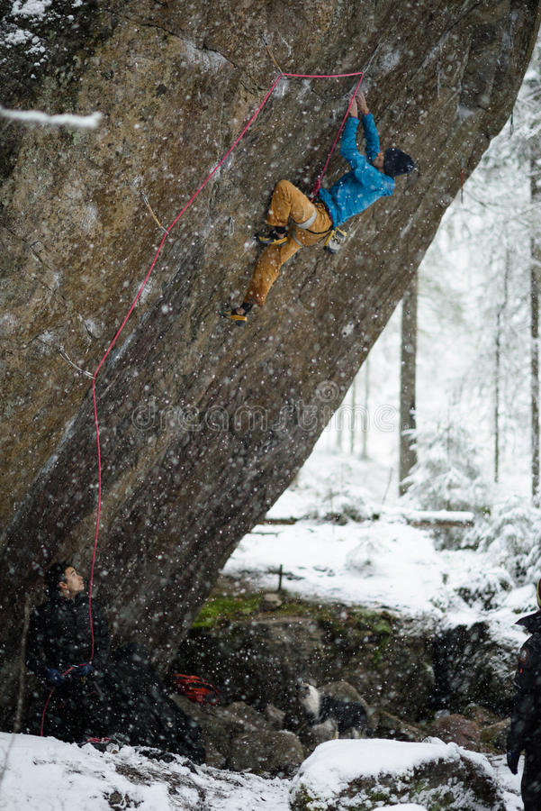Krańcowy zima sporta pięcie Młody męski rockowy arywista na rockowej ścianie Śnieżny las na tle obraz stock