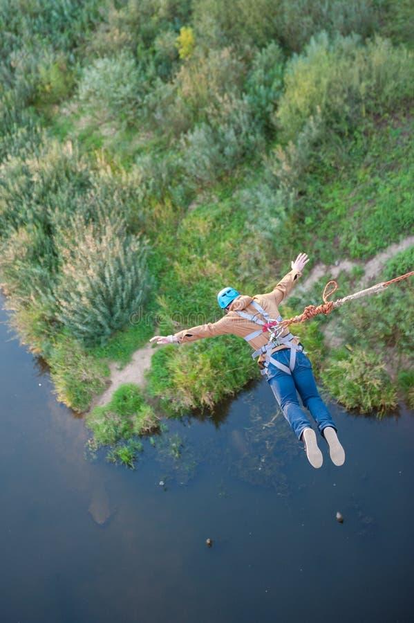 Kra?cowy skok od mostu M??czyzn skoki w bungee doskakiwaniu przy niebo parkiem zaskakuj?co szybko badaj? kra?cow? zabaw? Bungee w obraz royalty free