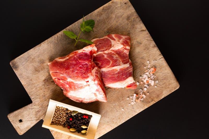 Kraag de zonder botten van het het stukvarkensvlees van het voedselconcept op scherpe raad met kruid op zwarte achtergrond met ex stock fotografie