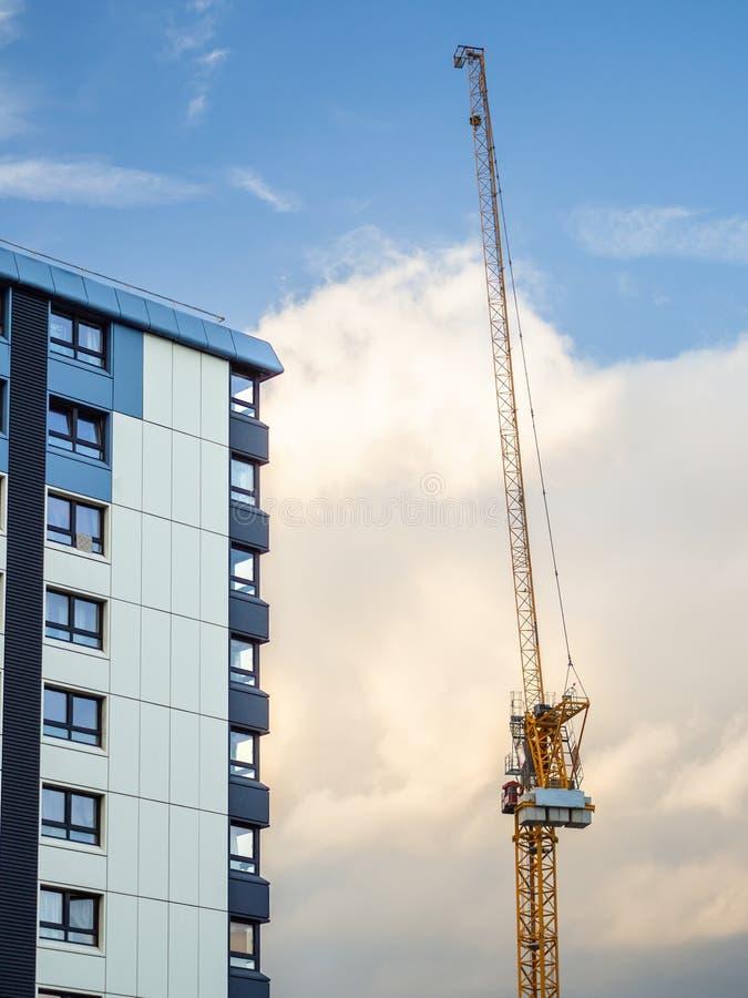 Kraan bij een bouwwerf van een geplaatst flatgebouw agains stock foto's