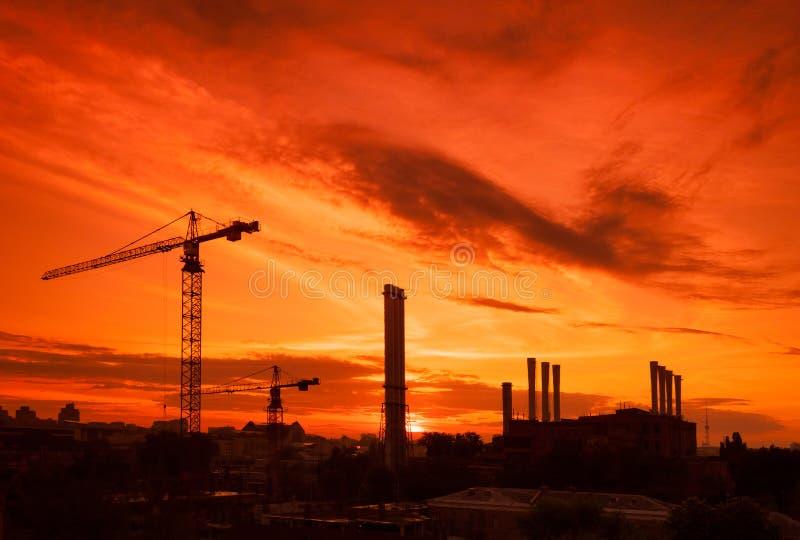 Kraan in de bouwwerf onder de zonsondergang royalty-vrije stock fotografie