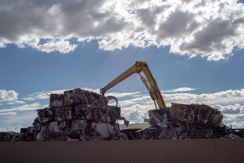 Kraan die cumes van samengeperst metaal bij het recycling van centrum stapelen royalty-vrije stock foto's
