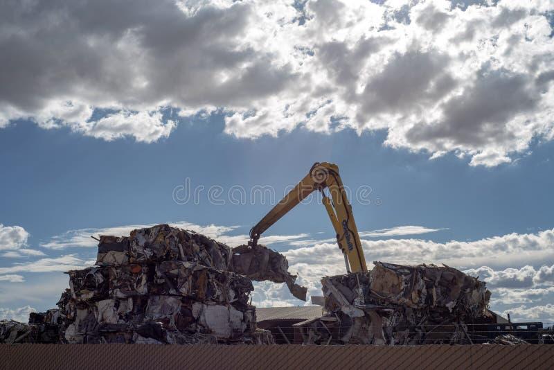 Kraan die cumes van samengeperst metaal bij het recycling van centrum stapelen stock foto