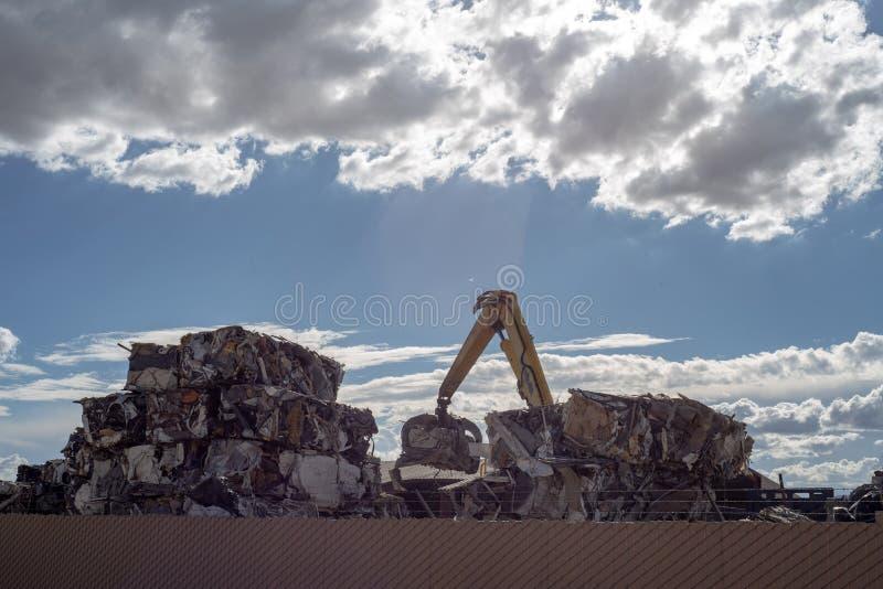 Kraan die cumes van samengeperst metaal bij het recycling van centrum stapelen royalty-vrije stock afbeelding